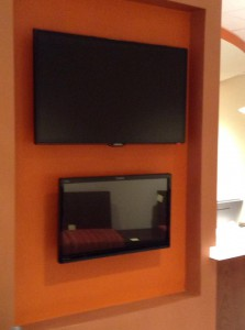 Touch screen signin terminal situated underneath a waiting area TV