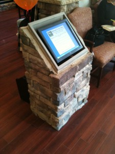 Touchscreen sign-in terminal inset into a masonry pedestal.